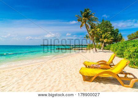 Beach chairs with umbrella at Maldives island, white sandy beach and sea