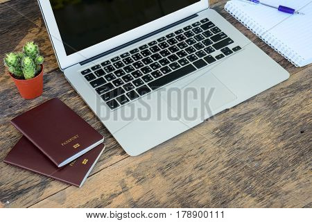 Laptop computer with passport book and notebook placed on wooden table work space
