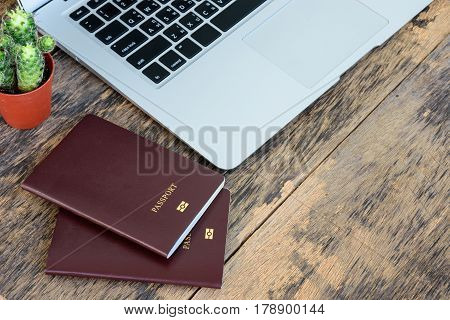 Laptop computer with passport book placed on wooden table work space