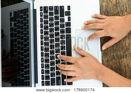 A woman hand typing on keyboard of laptop computer place on wooden table top view