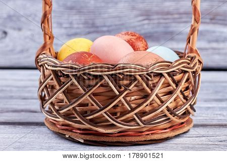 Easter wicker basket close up. Pile of chicken eggs.