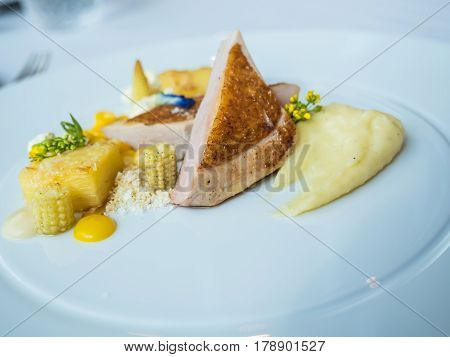 Cooked guinea fowl with mashed potato, corn, roasted almond