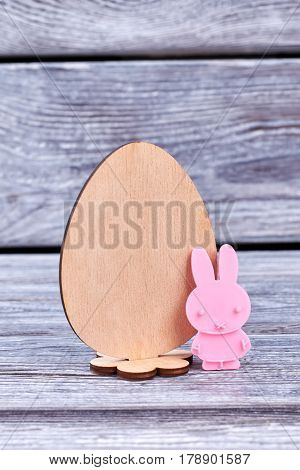 Plywood egg and plastic rabbit. Little pink bunny, wooden background. Easter handmade decorations.
