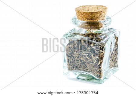 Dry cumin in glass bottle isolated on white background. Closeup macro shot.
