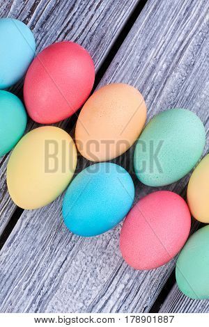 Bright eggs on gray wood. Diagonal rows of Easter eggs,