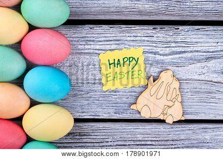 Colored eggs, plywood rabbits cutout. Yellow greeting card.