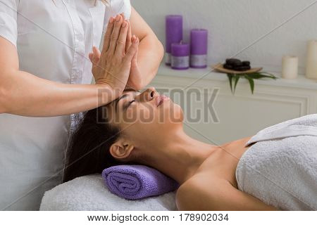 Head and face pummeling massage in spa. Female beautician work in wellness center. Professional massagist make relax healthy procedure to beautiful indian girl in cosmetology cabinet or beauty parlor.