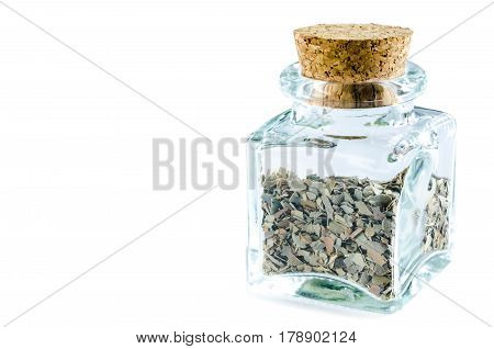 Dry crushed bay leaf in glass bottle isolated on white background. Closeup macro shot.