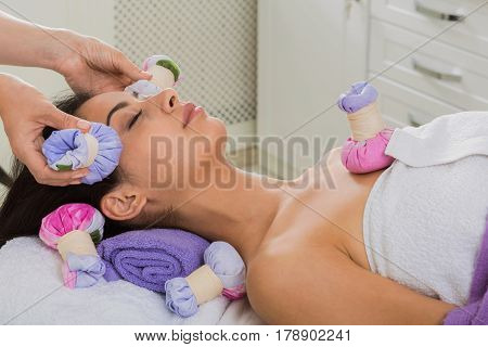 Herbal ball face massage in ayurveda spa. Female massagist with young woman in wellness center. Healthcare therapy to beautiful indian girl in beauty parlor, side view of face with eyes closed