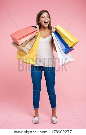 Glad woman with shopping bags in hands, looks glad after good shopping on sales