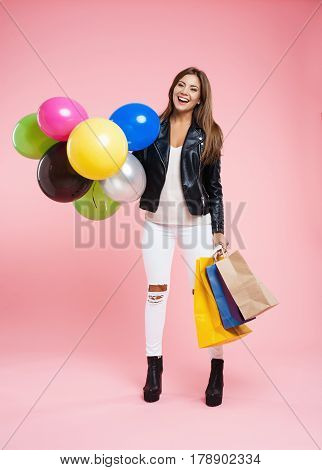 Pretty girl in trendy spring and autumn outfit looks glad holding birthday presents and balloons