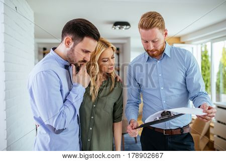 Male consulant showing property contract to the couple.
