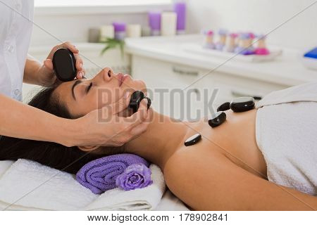 Black marble stone massage in ayurvedic spa. Beautiful girl in wellness center. Professional relaxation procedure to attractive young indian girl in beauty parlor. Side view