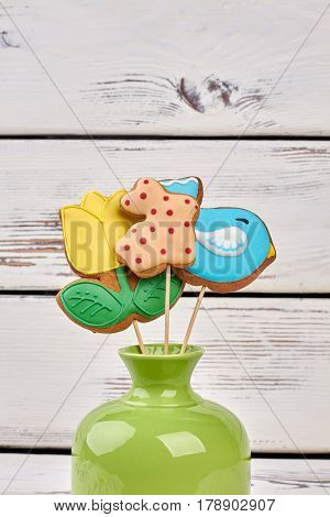Vase and cookies on sticks. Biscuits with colorful glaze. Cute Easter desserts.