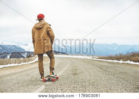 Stylish happy Young man in a cap and trousers joggers rolling down a mountain road on a longboard, enjoying life