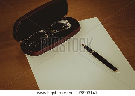 Financial charts pen and glasses.a sheet of white paper
