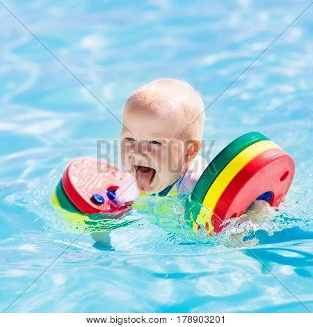 Happy laughing little baby boy playing in outdoor swimming pool on a hot summer day. Kids learn to swim. Child with colorful floaties. Swimming aid for kid. Family vacation in tropical resort.