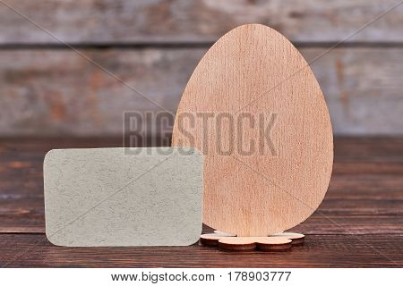 Plywood egg and blank card. Empty paper on wooden surface. Easter message ideas.