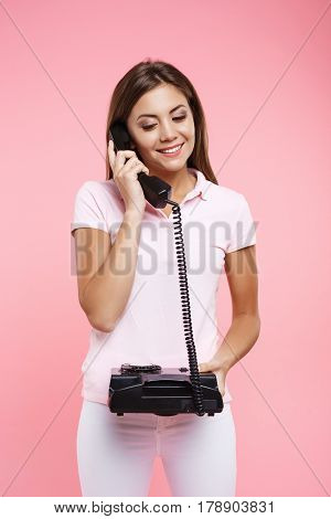 Portrait of beautiful woman in bright sportswear making phonecalls, holding old balck landline, looking down