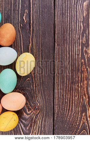 Colored eggs on brown wood. Easter eggs with copyspace.