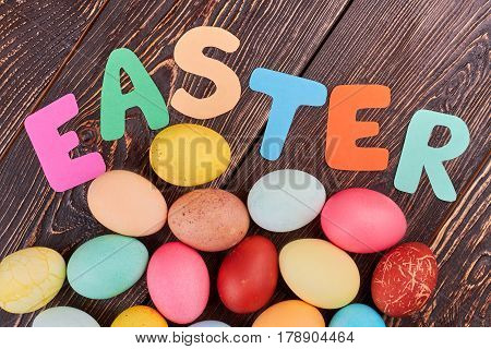 Easter lettering on brown wood. Paper letters and colored eggs. Holidays and traditions of Christianity.