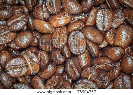 Coffee beans closeup. Roasted brown coffee beans texture, coffee beans background for design. Dark edged.