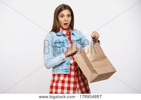 Beautiful stylish girl in fashion check dress looking amazed and overwhelmed after opeining paper bag