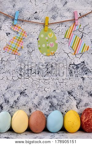 Paper cutouts, rope and clothespins. Row of painted eggs. Easter home decor ideas.