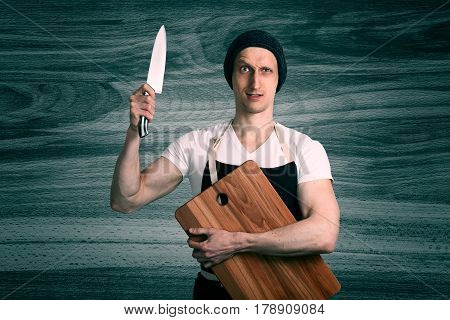 A chef with a large knife and wooden cutting board in his hands. Studio portrait closeup