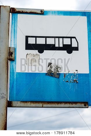 Old Wretched Grungy Bus Sign On Blue Sky With Clouds