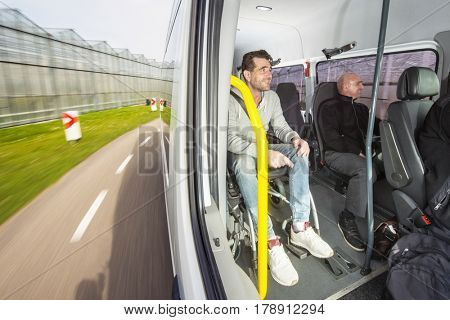 Disabled person, sitting in a wheel chair on the road as passenger in a modified taxi bus, taking a tour through the country side
