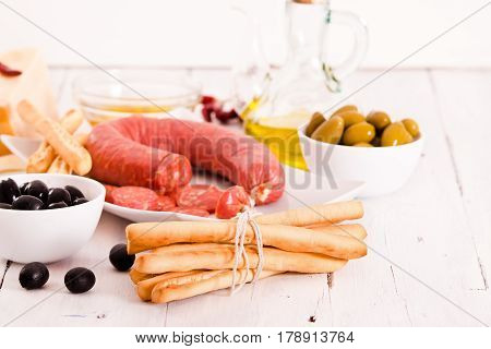 Grissini breadsticks with salami on wooden table.