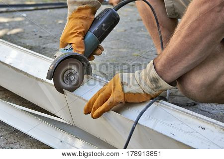 Worker hands with gloves using metal saw