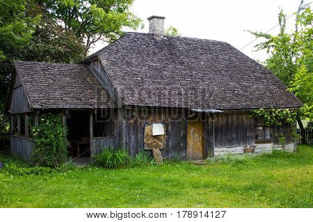 Old wooden countryside house with wooden roof with green grass garden