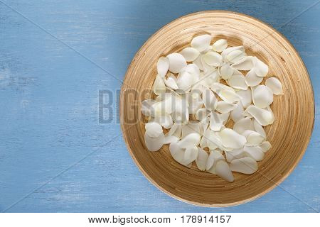 Petals of white roses on blue painted rustic background. Fresh natural flowers in bowl. Dirty grunge wooden board.