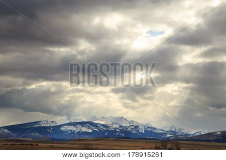 Large Montana valley with farm land and snow-capped peaks.