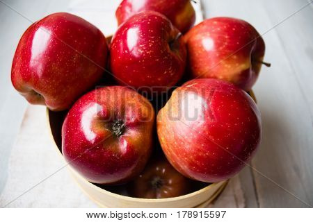 a red apples on in wooden bowl
