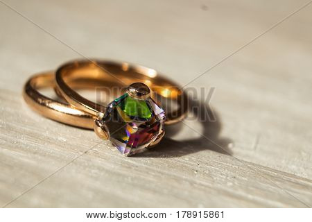 golden rings with shiny stone on wooden background