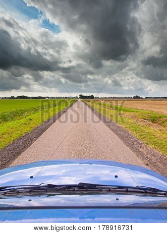 Blue Car on a Long Straight Road with Dark Cloudy Sky as a Concept for an Uncertain Economic Future