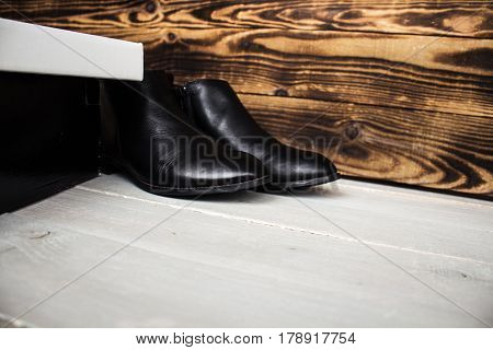 the boots and shoes box on wooden background