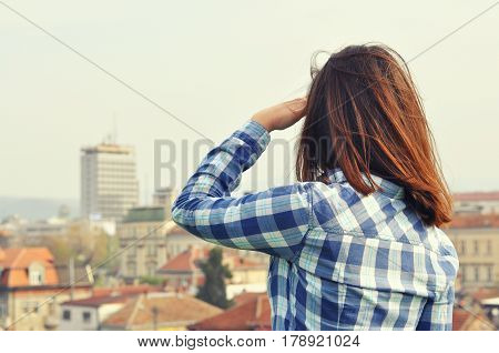 Beautiful traveler girl enjoying the view of  city skyline. Beautiful view of the city from above.