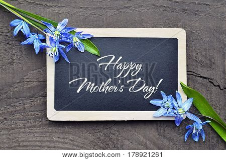 Happy Mother's Day.Chalkboard and first spring flowers on old wooden background.Mother's Day greting card.