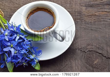 Coffee cup and bouquet of first spring flowers on old rustic wooden table. Coffee mug and scilla flowers. Spring morning, breakfast, good morning concept. Selective soft focus.
