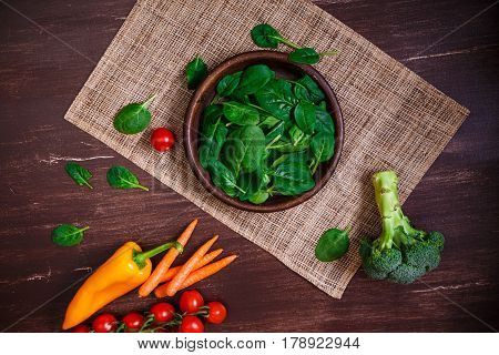 Spinach leaves in bowl. Carrot, pepper and cherry tomatoes, brocoli. Raw fresh vegetable. Fresh natural plant leaf. Organic food on wooden table.