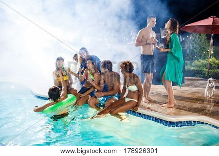 Young cheerful friends smiling, rejoicing, resting at party near swimming pool. Copy space.
