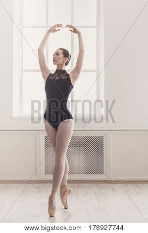 Classical Ballet fifth position near large window in light hall. Ballerina training, high-key soft toning. Vertical image