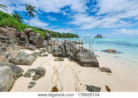 Tropical beach Anse Royale with granite boulders in the foreground at Mahe island Seychelles - vacation background.