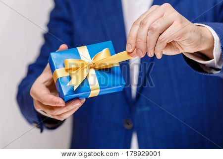 Male hands holding a gift box. Present wrapped with ribbon and bow. Christmas or birthday blue package. Man in suit and white shirt.
