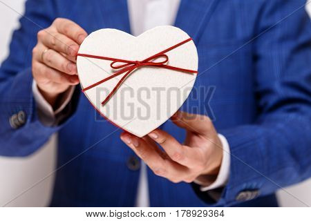 Male hands holding heart-shaped gift box. Present wrapped with ribbon and bow. Valentines day love package. Man in suit and white shirt.