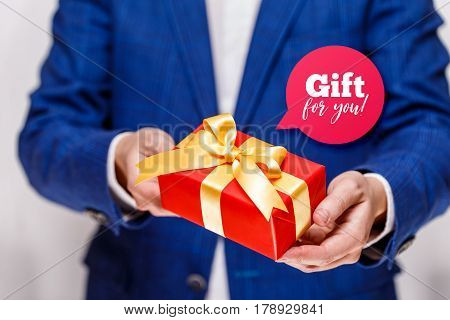 Male hands holding a gift box. Present wrapped with ribbon and bow. Gift for you speech bubble. Man in suit and white shirt.
